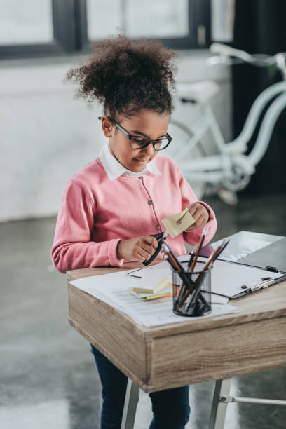 Cute little girl in eyeglasses holding scissors and cutting paper at office table stock photo