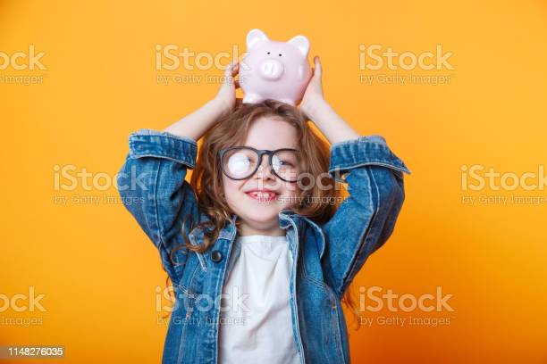 Cute little girl in eyeglasses shaking piggy box on orange background picture id1148276035?b=1&k=6&m=1148276035&s=612x612&h=l64uuo mnlpji a6t8fjldcyfmflawzw9nhxgmoaaz4=