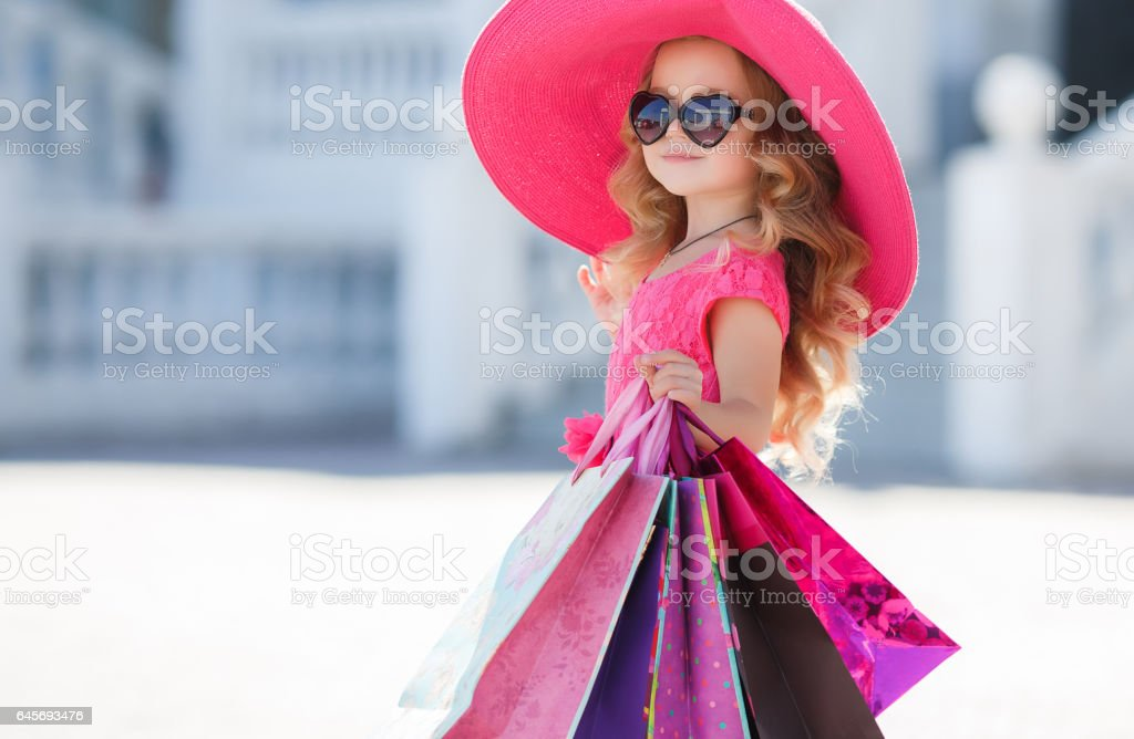 Cute little girl in fashion hat with shopping bags next to a supermarket stock photo