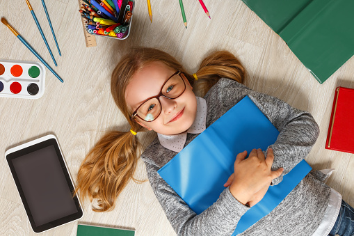 Cute little girl in glasses with a book lying on the floor. A child is surrounded by a book, tablet, paints, brushes, pencils.