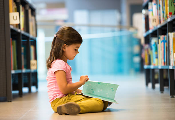 Cute Little Girl In Library Cute Little Girl In Library. spelling stock pictures, royalty-free photos & images