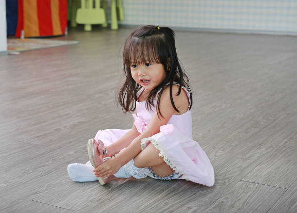 Cute little girl in pink dress sitting on floor tries to put on her shoes in the playroom. stock photo