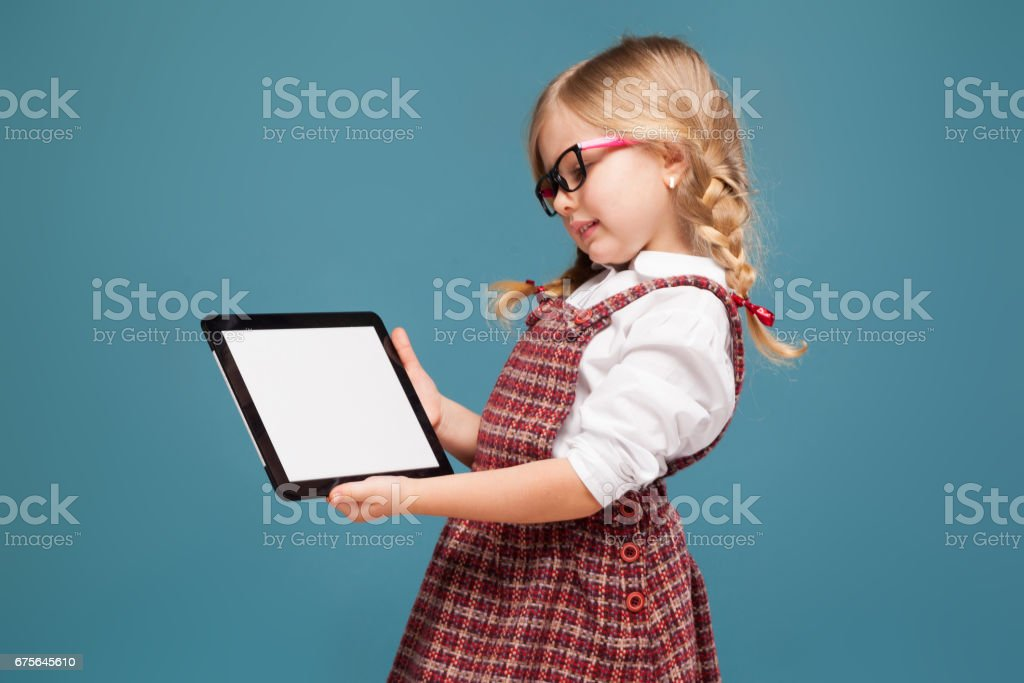 Cute little girl in red dress, white shirt and glasses holds empty tablet royalty-free stock photo