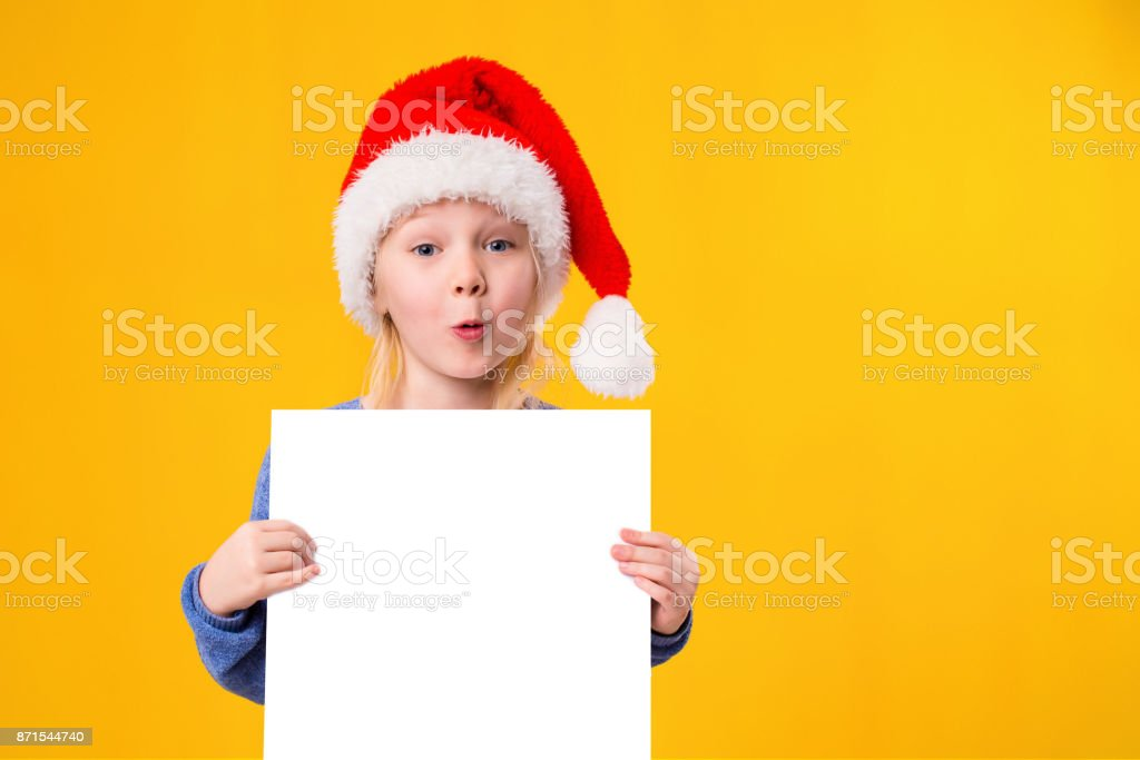 63c25f12e05 Cute little girl in Santa Claus hat with a white blank paper sheet.  Christmas