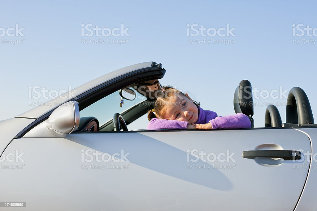 Cute Little girl in sport car at sidelight royalty-free stock photo
