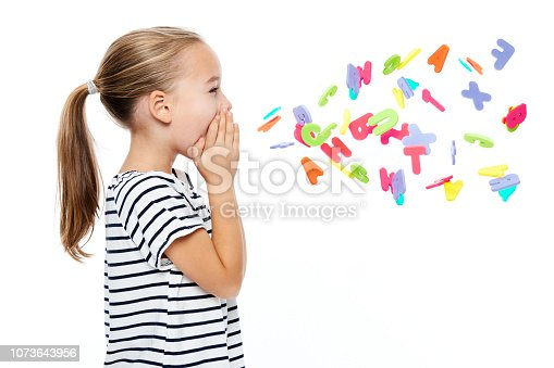 istock Cute little girl in stripped T-shirt shouting out alphabet letters. Speech therapy concept over white background. 1073643956