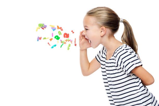 Nettes kleines Mädchen in gestreiftem T-Shirt schreien Alphabet Buchstaben. Sprachtherapiekonzept über weißem Hintergrund. – Foto
