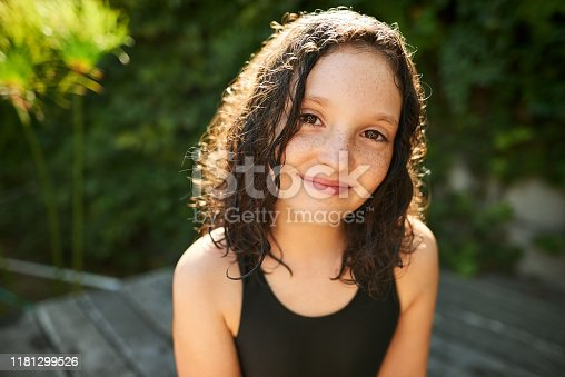Shot of a cute little girl in swimwear sitting by the pool outdoors