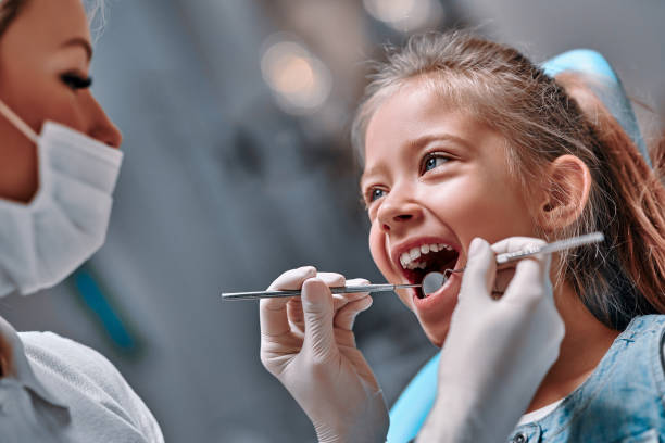 Cute little girl in the dentist chair stock photo