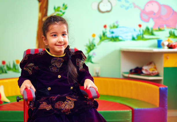 cute little girl in wheelchair at rehabilitation center for kids with special needs - foto stock