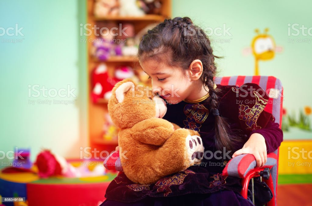 cute little girl in wheelchair telling her secret to plush bear in kindergarten for kids with special needs - foto stock