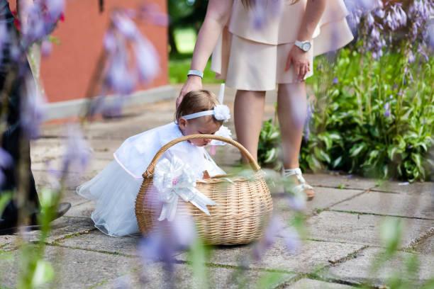 niedliche kleine mädchen im weißen kleid mit korb und kerze vor kirche. kleinen blumenmädchen bei hochzeit. - geschenk zur taufe stock-fotos und bilder