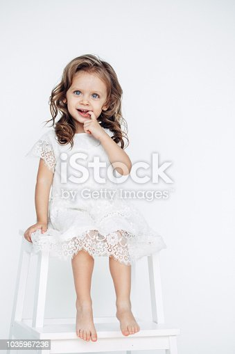 1035967418 istock photo Cute little girl in white dress smiling on camera 1035967236
