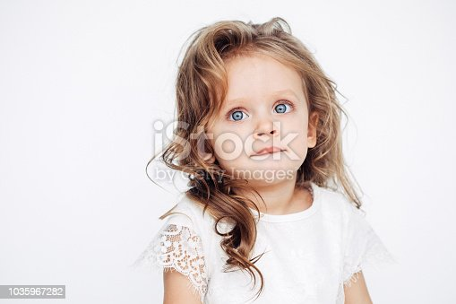 1035967418 istock photo Cute little girl in white dress smiling on camera 1035967282