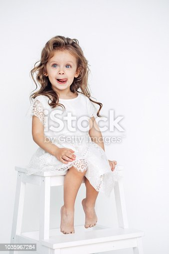 1035967418 istock photo Cute little girl in white dress smiling on camera 1035967284