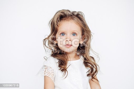 1035967418 istock photo Cute little girl in white dress smiling on camera 1035967318
