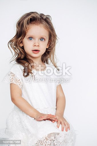 1035967418 istock photo Cute little girl in white dress smiling on camera 1035967388