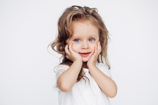istock Cute little girl in white dress smiling on camera 1035967418