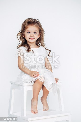 1035967418 istock photo Cute little girl in white dress smiling on camera 1035967484