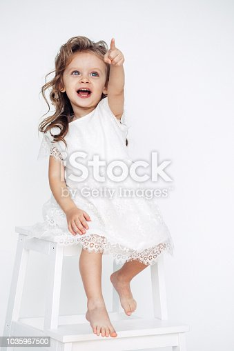 1035967418 istock photo Cute little girl in white dress smiling on camera 1035967500