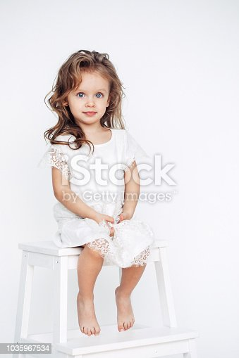 1035967418 istock photo Cute little girl in white dress smiling on camera 1035967534