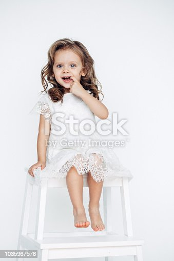 1035967418 istock photo Cute little girl in white dress smiling on camera 1035967576
