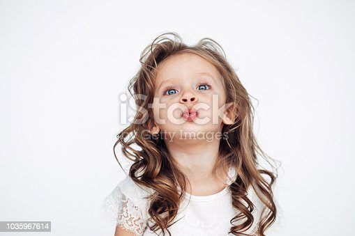 1035967418 istock photo Cute little girl in white dress smiling on camera 1035967614