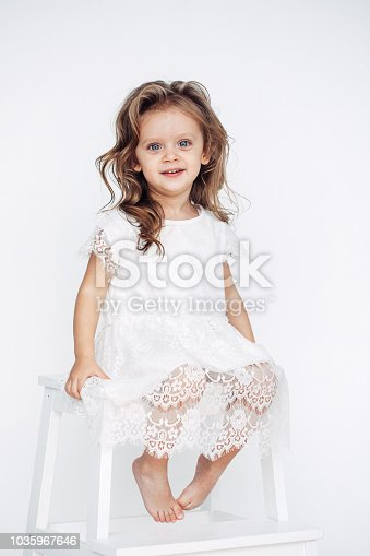 1035967418 istock photo Cute little girl in white dress smiling on camera 1035967646