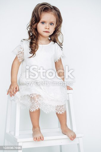 1035967418 istock photo Cute little girl in white dress smiling on camera 1035967696