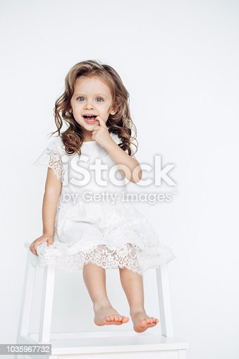 1035967418 istock photo Cute little girl in white dress smiling on camera 1035967732