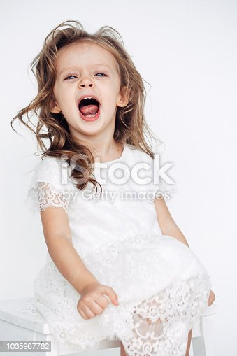 1035967418 istock photo Cute little girl in white dress smiling on camera 1035967782