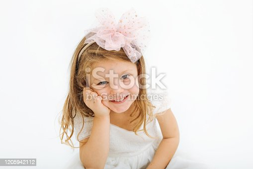 1035967418 istock photo Cute little girl in white dress smiling on camera 1205942112