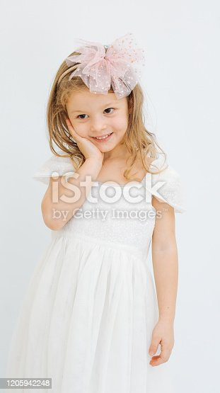 1035967418 istock photo Cute little girl in white dress smiling on camera 1205942248