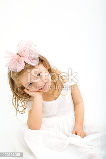 1035967418 istock photo Cute little girl in white dress smiling on camera 1205942551
