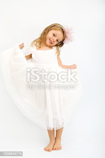 1035967418 istock photo Cute little girl in white dress smiling on camera 1205943775