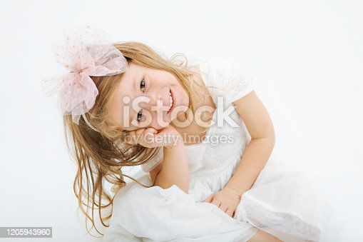 1035967418 istock photo Cute little girl in white dress smiling on camera 1205943960