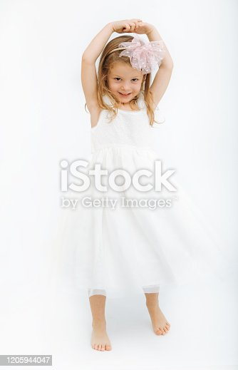 1035967418 istock photo Cute little girl in white dress smiling on camera 1205944047