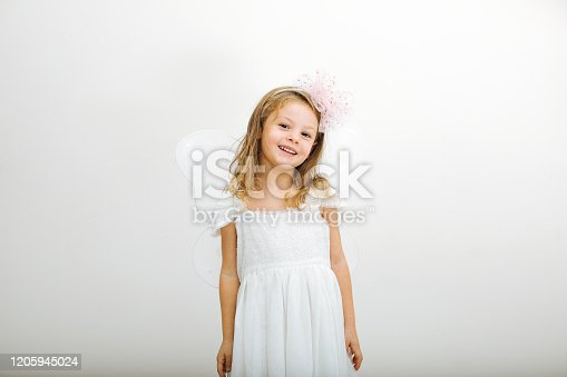 1035967418 istock photo Cute little girl in white dress smiling on camera 1205945024