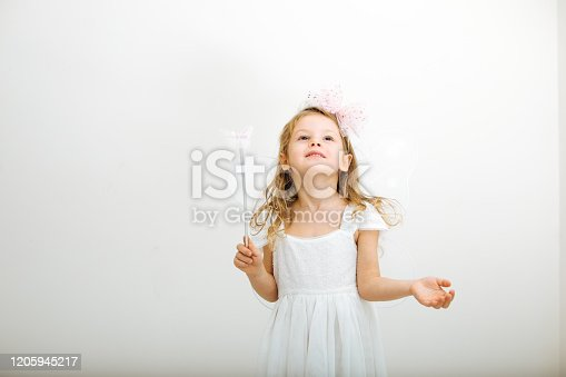 1035967418 istock photo Cute little girl in white dress smiling on camera 1205945217