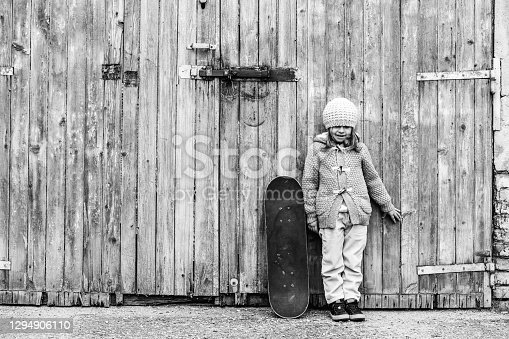 Cute little girl in winter wool clothes with skateboard while standing against grunge wooden background - Concept of activity and playful childhood - Copy promo space - Black and white retro style