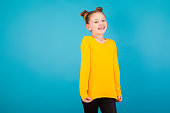 isolated on blue, adorable red-haired girl with freckles in lemon sweater and black trousers, shrugging and looking into the camera. copyspace.