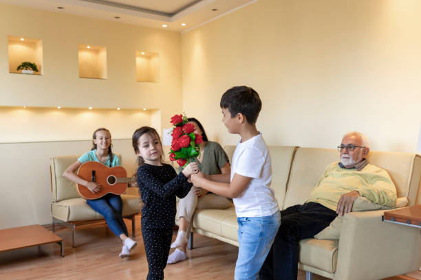 Cute Little Girl is Celebrating her Birthday while Receiving the Red Roses from her Brother. Happy Family at the Birthday Party. Multi-Generation Family is Enjoying in Time Together and is Listening to Guitar Playing by Young Girl. group of friends giving gifts to the birthday girl stock pictures, royalty-free photos & images