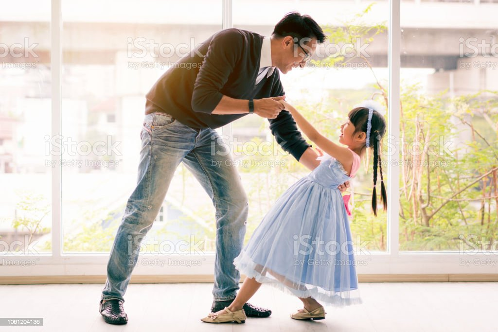 Cute little girl is dancing with her daddy. Having fun at home together concept royalty-free stock photo