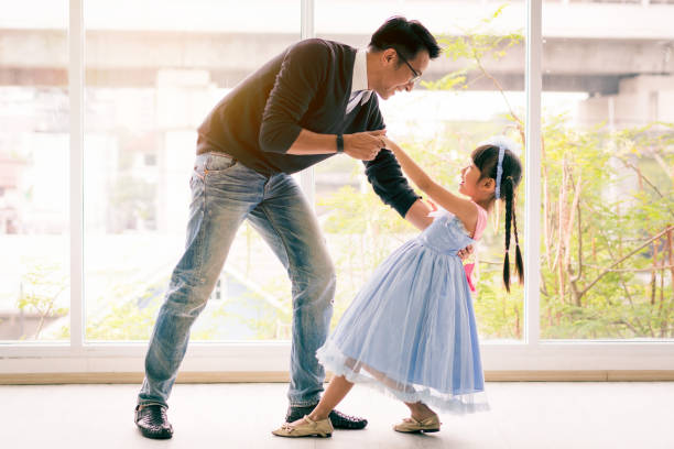 cute little girl is dancing with her daddy. having fun at home together concept - father and daughter stock photos and pictures