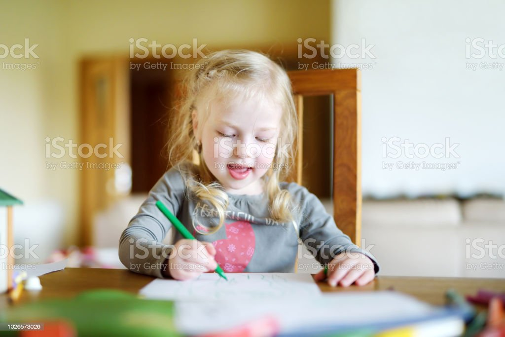 Cute little girl is drawing with colorful markers stock photo