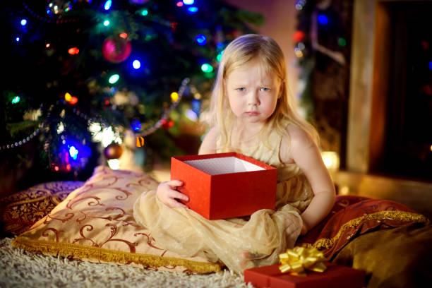 Nettes kleines Mädchen ist unglücklich mit ihrem Weihnachtsgeschenk – Foto