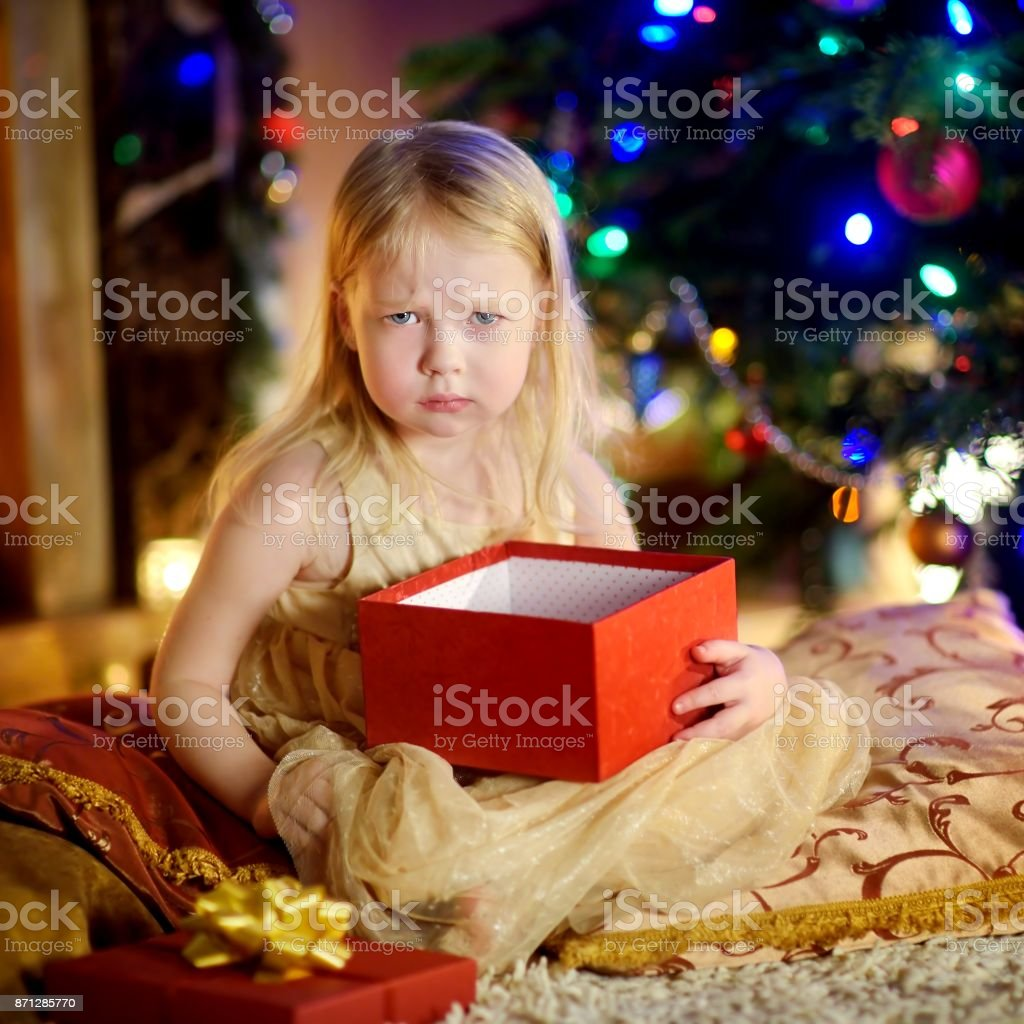 Cute little girl is unhappy with her Christmas gift stock photo