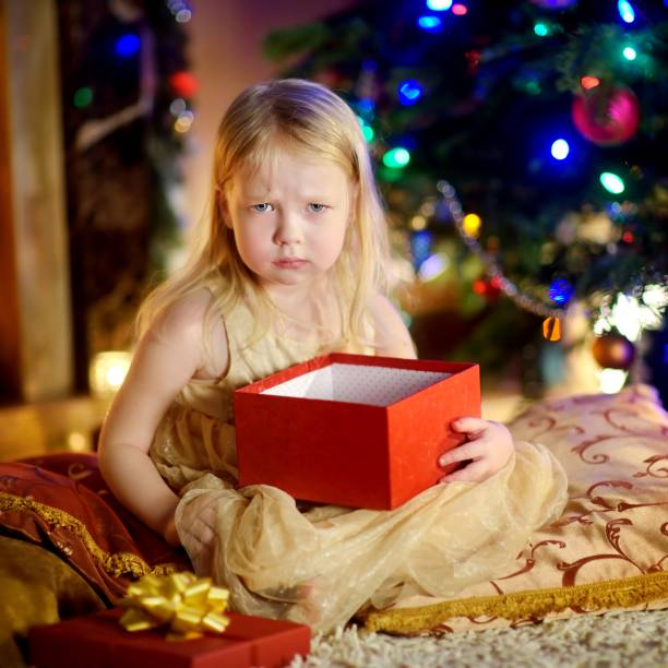 cute little girl is unhappy with her christmas gift - disappointment stock pictures, royalty-free photos & images