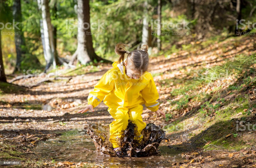 Cute little girl jumping in muddy puddle stock photo