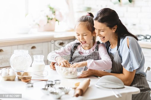 Excited little girl kneading the dough in bowl, helping mother in baking, copy space